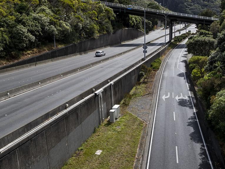 A view of a nearly empty motorway, with bridges crossing it, also empty of cars