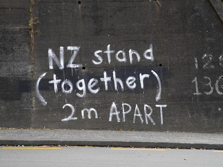 "Graffiti on a concrete wall beside a road. It says ""Stand Together (2m apart)"""