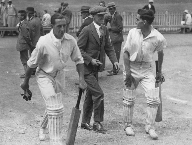 Men walking away from cricket ground