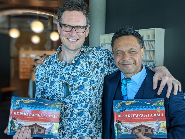 Two men smile while holding books