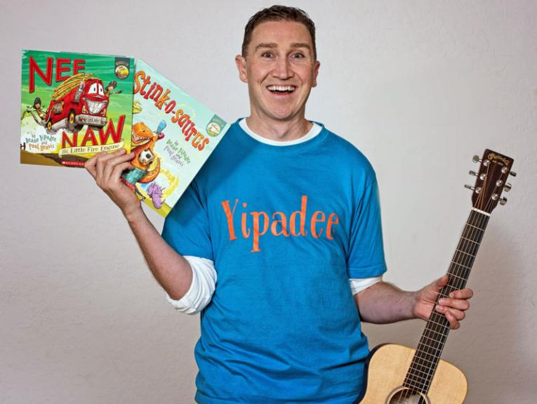 A man smiles holding books and a guitar