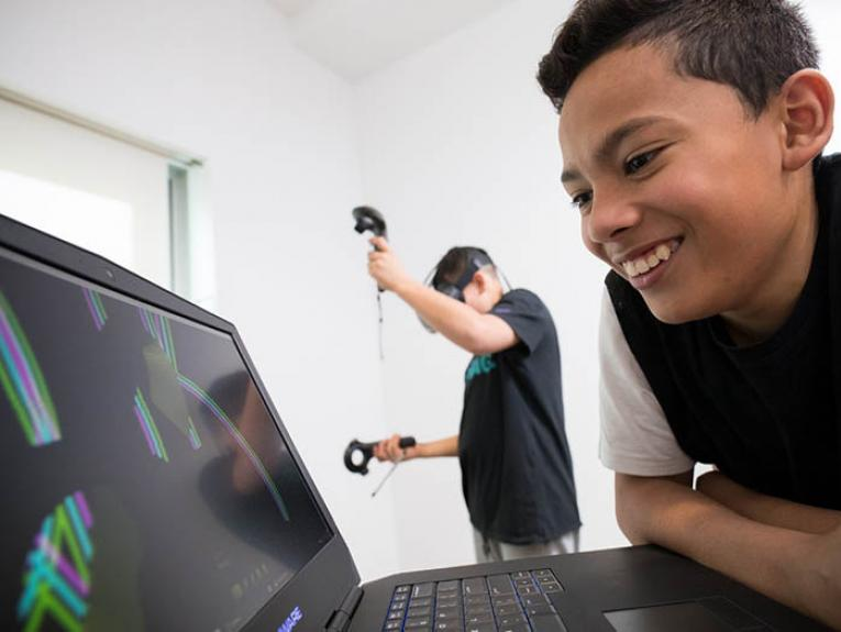 Child looking at computer screen. Another child is in the background drawing in 3 dimension