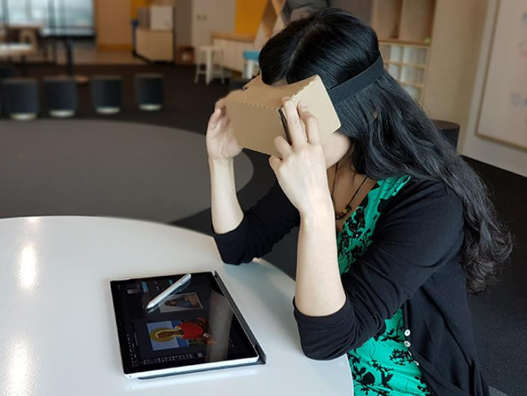 A student uses a Google cardboard to experience virtual reality