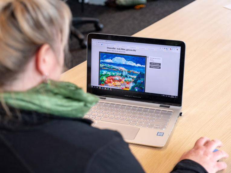 A person on a laptop looking at images on Te Papa's Collections Online website