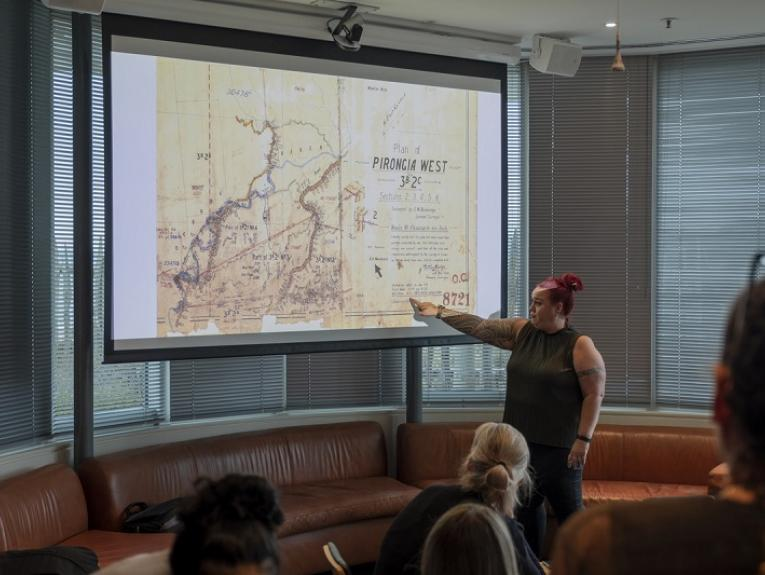 A woman is standing in front of a large screen and pointing at a place on a map in front of an audience.