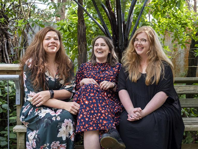Three women sitting in Bush City surrounded by trees