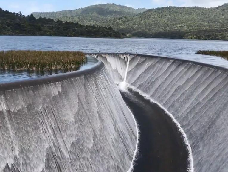 A lake with a man-made channel in the middle of it with water flowing down both sides