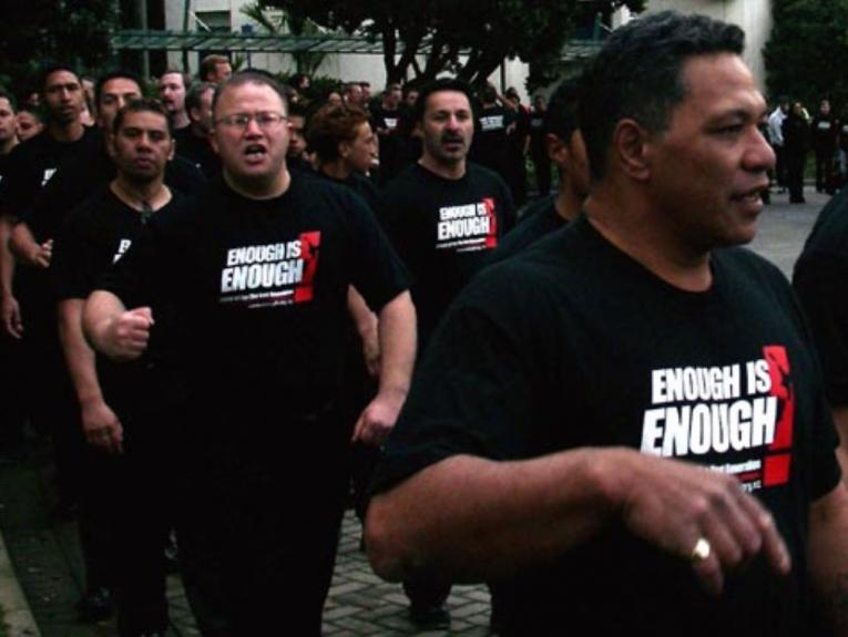Men marching with black t-shirts that say 'enough is enough'