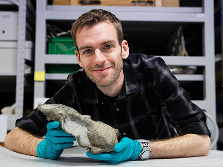 A smiling Felix Marx holds a seal skull in his hand