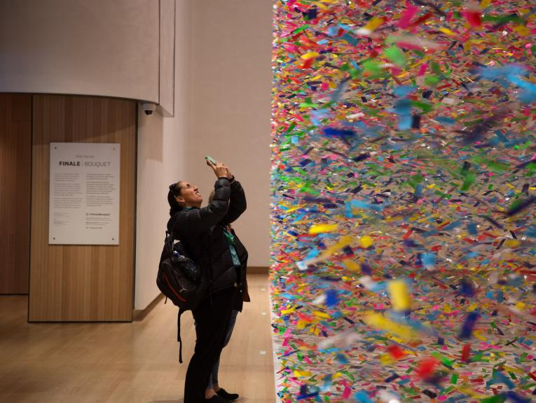 A visitor trying to capture the scale of a colourful artwork