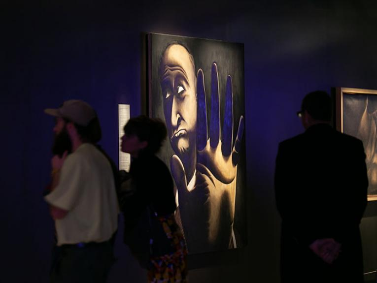 People look at a painting by Tony Fomison. The painting depicts a man holding his hand up to the camera as if to say No