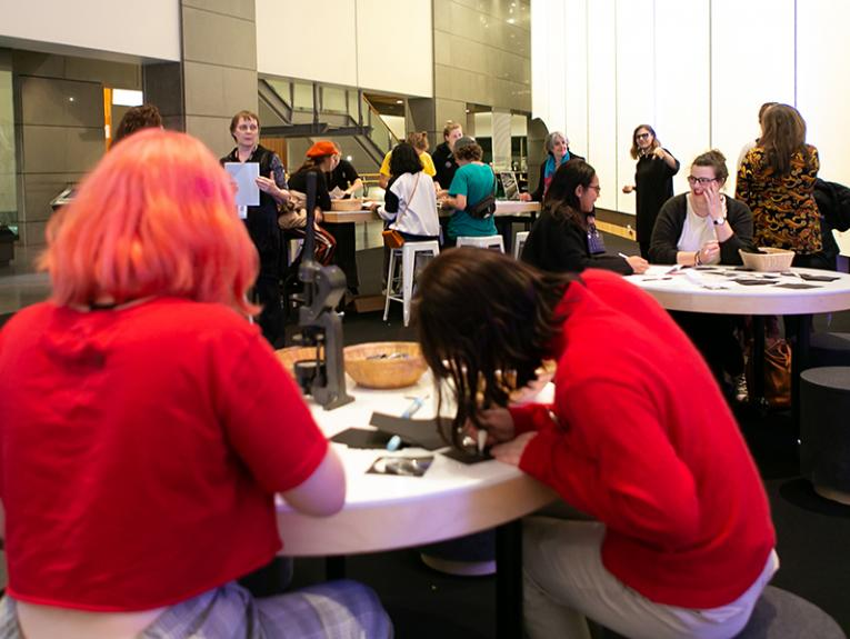 People sitting and making things at tables in a foyer, there are some people standing and observing in the background