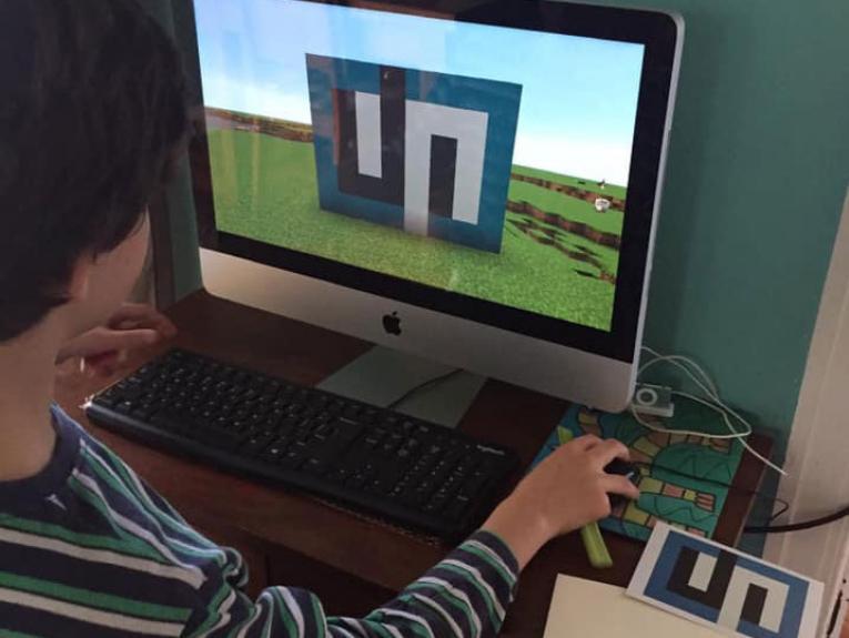 A little boy copies an artwork in a Minecraft game