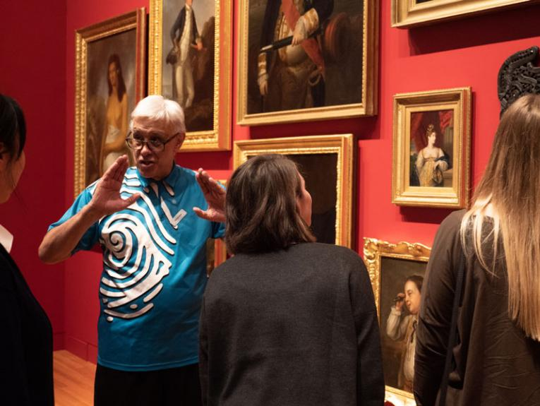 A guided tour happening in front of lots of paintings