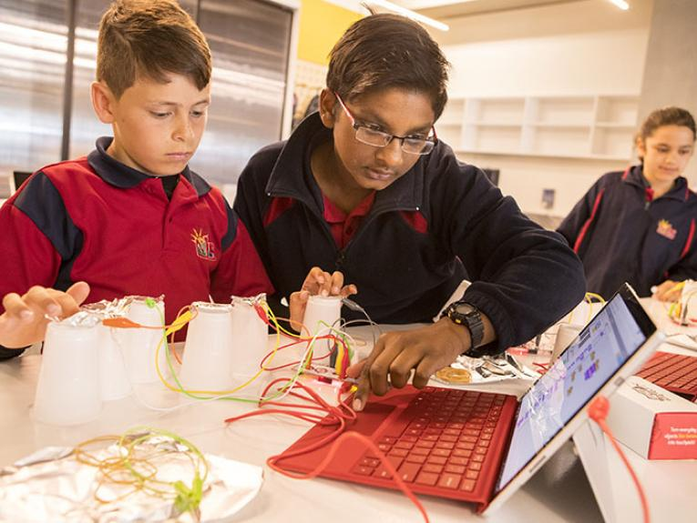 Students play with a computer