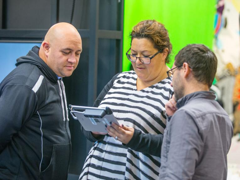 Teachers crowd look at a tablet with a Te Papa educator