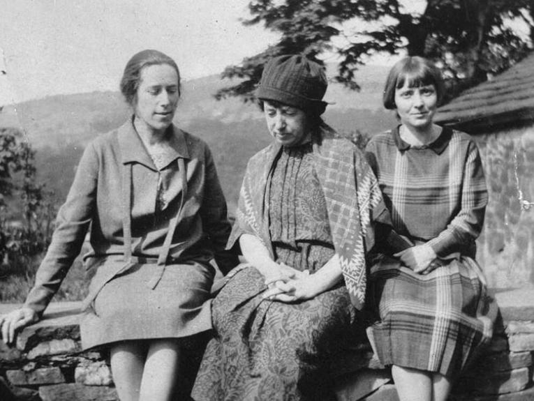 Three women sit on a low brick fence, with a farmhouse-style building behind them to the right. Frances Hodgkins is in the middle, looking somewhat despondent
