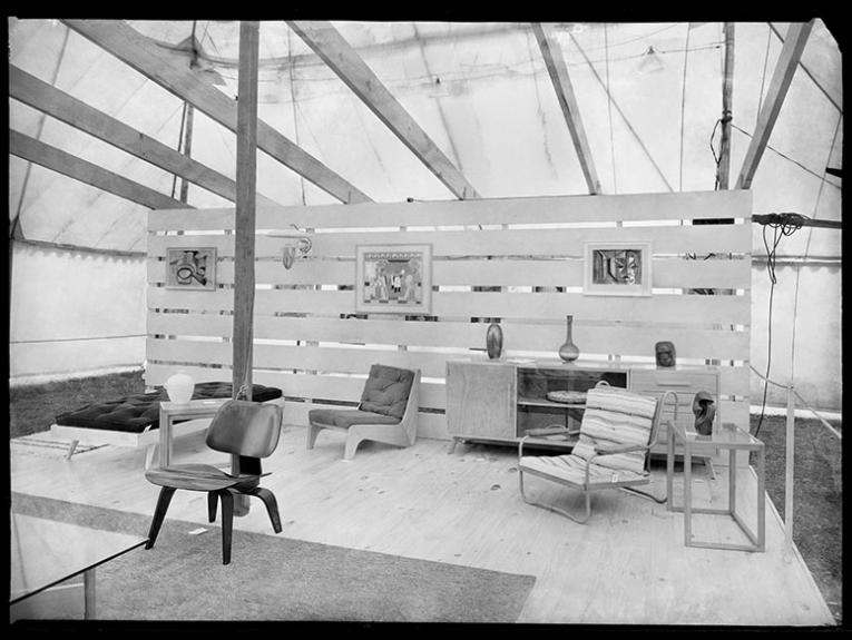 Display of a mid-century living room set up in an exhibition, with chairs, painting on the wall, and a sideboard