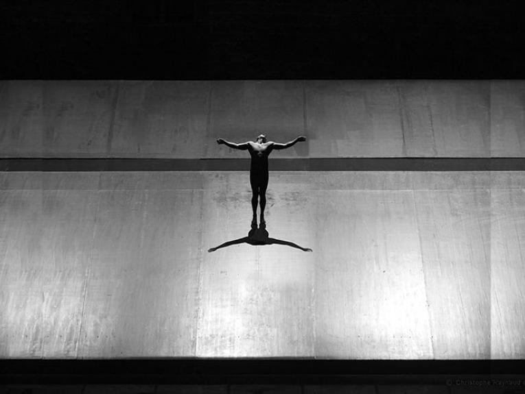 A naked man poses Christ-like against a backdrop of concrete