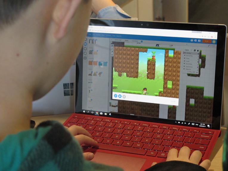 A boy uses a computer to design a game