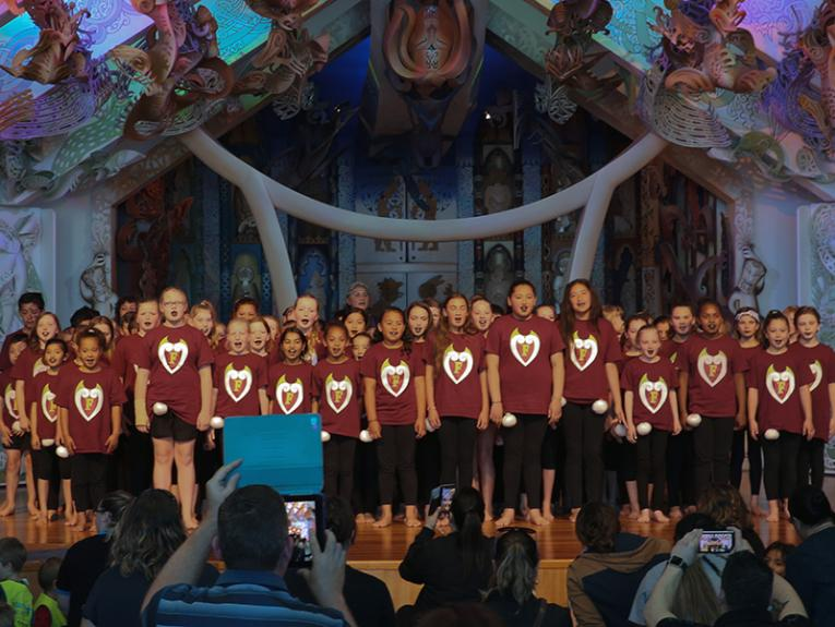 A group of children standing on a stage facing the audience and singing