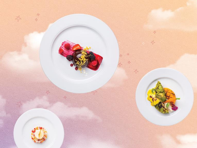 Plates of food float in a pink and orange sky