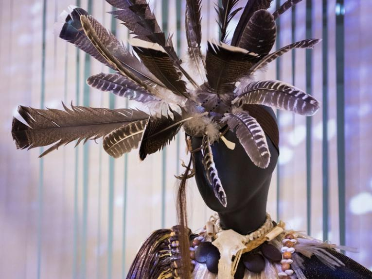 Mannequin dressed in Pacific inspired outfit with large feather headress
