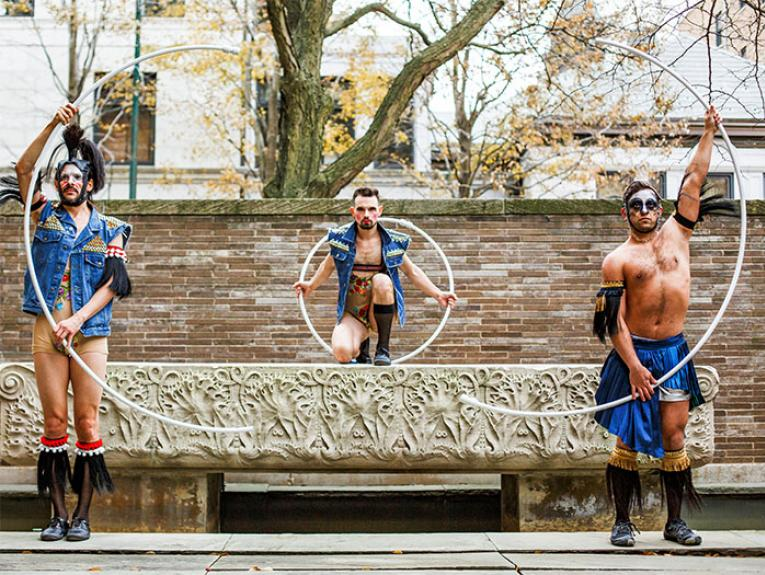 Three male performers stand holding acrobatic hoops