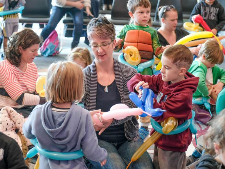 A mother helps her children in a balloon workshop