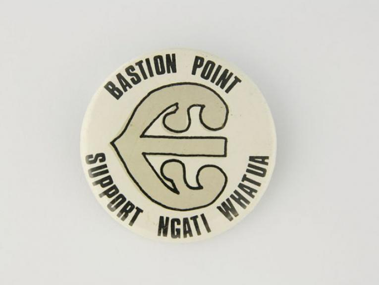 A round badge with 'Bastion Point is Maori Land' on it.