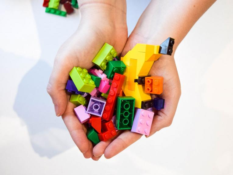 Hands holding Lego