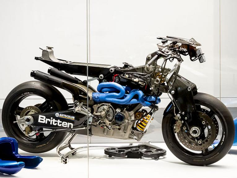 A motorbike on display in a large glass case