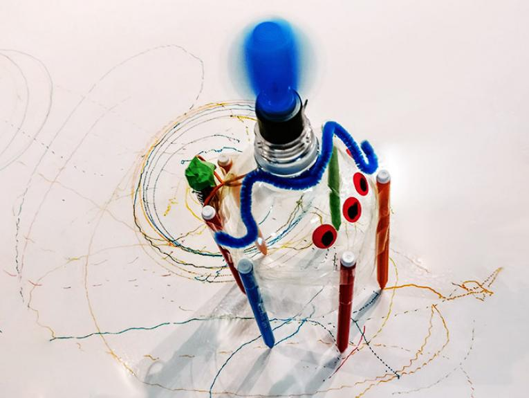 A robot made from a plastic cup and pens