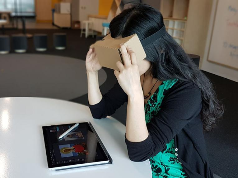 A woman uses a Google Cardboard virtual reality headset
