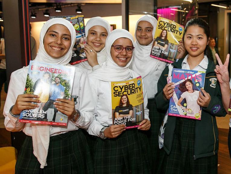 Girls holding technology magazines