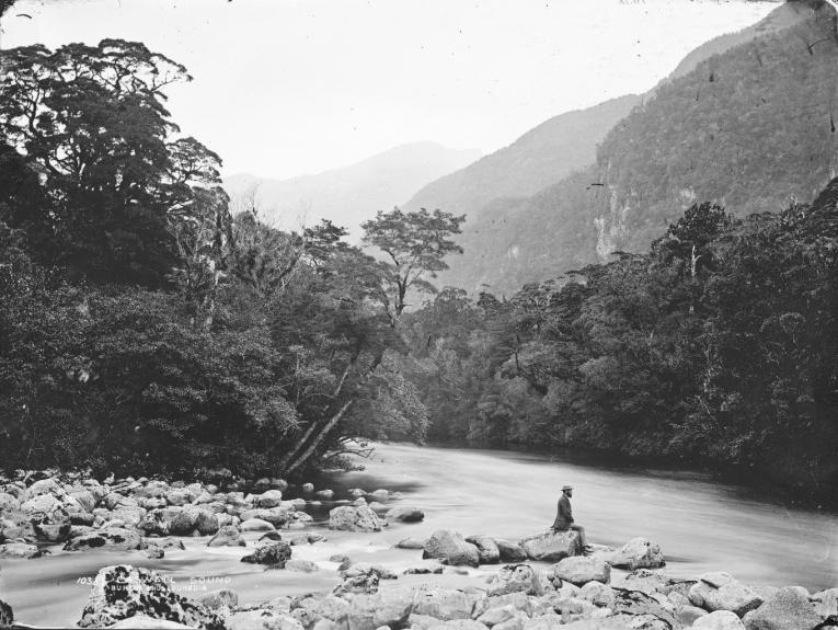 A man sits on a rock by the river