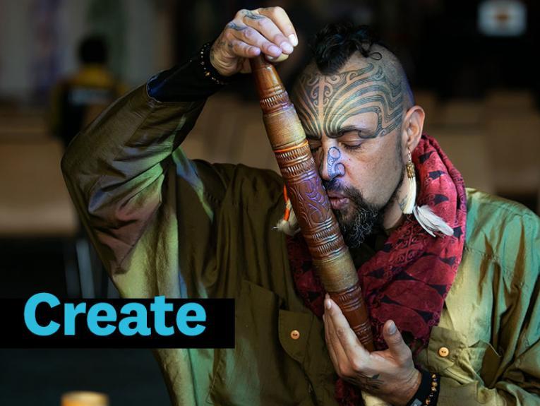 Man plays a pūtōrino, a Māori musical instrument