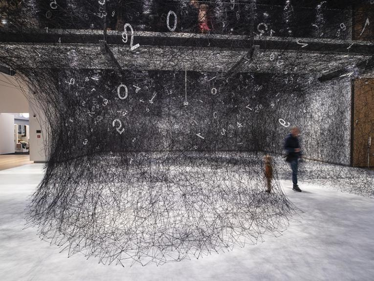 Two blurry people walking through a large web of wool that has white numbers scattered through it.