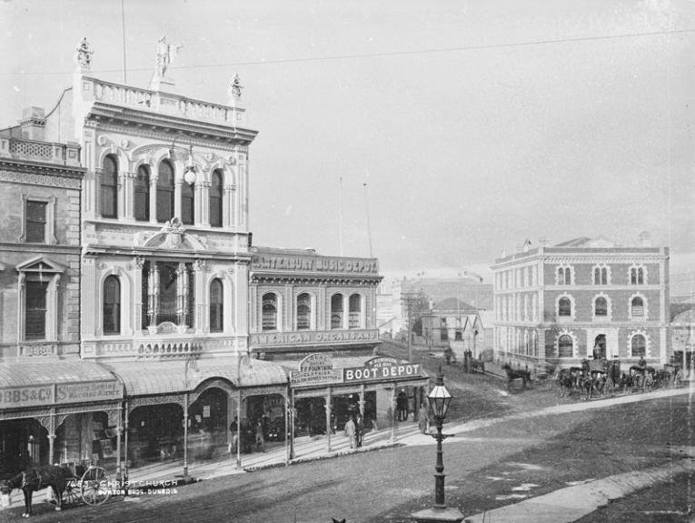 Black and white photo of ornate buildings, you can see a horse and cart