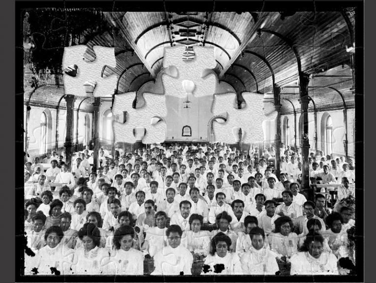 Black and white photo of Sāmoan people dressed in white in a wooden church with high arches.
