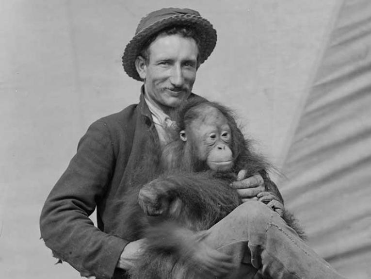 Man sits with an orangutan