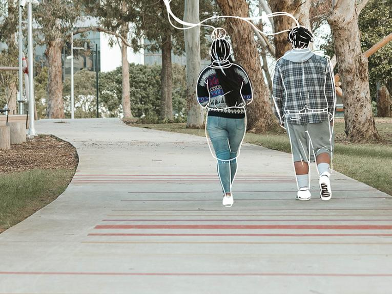 Two people walking along a path away from the camera, there are white outlines drawn around the poeple's cloting