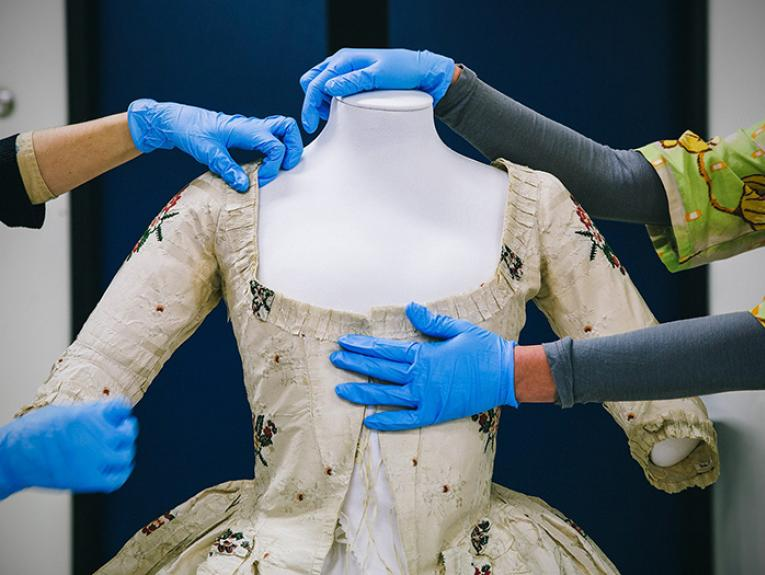 Textile Conservators put the finishing touches on an 18th century gown