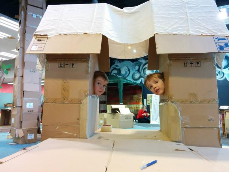 Two boys peer out from cardboard box structures