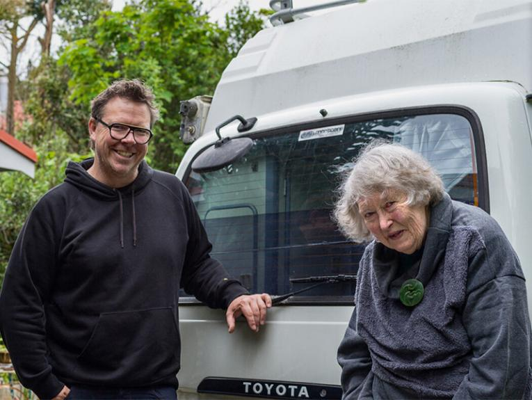 A man and a woman standing in front of a white van looking at the camera