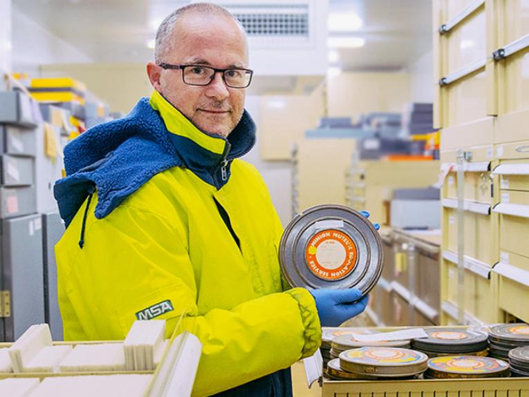 David Riley in the cold store holding one of the film archives