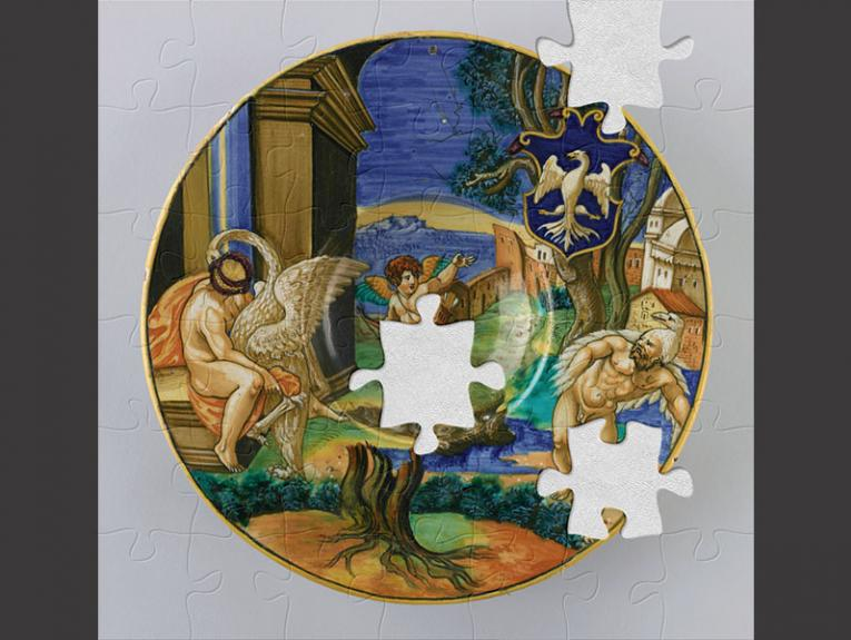 Ornamental plate with gold rim and a scene painted on it depicting a cherub and two men with swans
