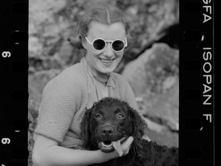 A woman with a dog. The dog's eyes are crossed and his tongue is out