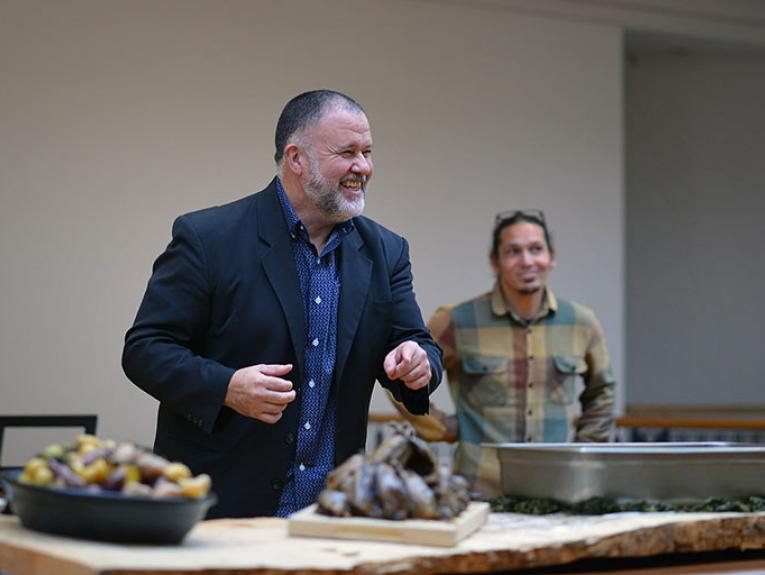 Two men stand smiling over an array of food