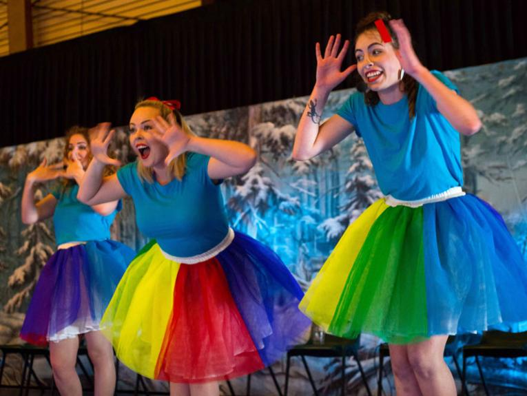 Three women dress in rainbow coloured ballet tutus